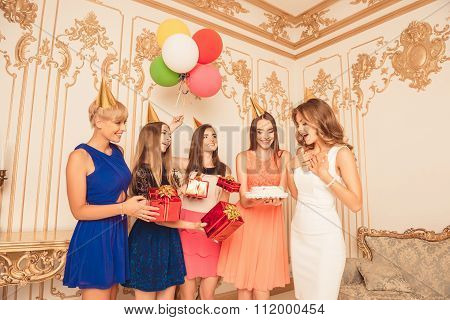Cheerful Girls Holding Balls And  Presents Showing Birthday Cake