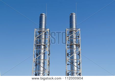 Two metal chimneys blue dots over bright sky