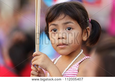 BANGKOK, THAILAND, JANUARY 23, 2012 : Portrait of a Thai little girl in the crowd, waiting for the Chinese new year show in Chinatown of Bangkok, Thailand