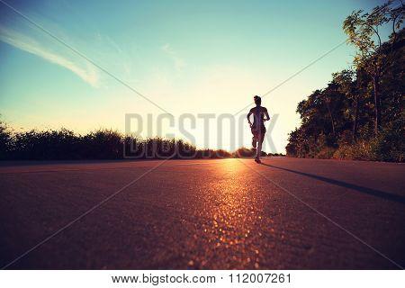 young fitness woman runner running on sunrise seaside