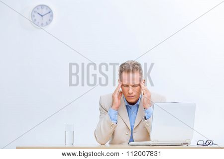 Stressed office worker having a headache.