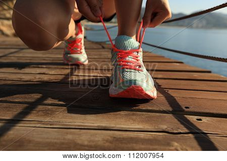 young woman runner tying shoelace on seaside