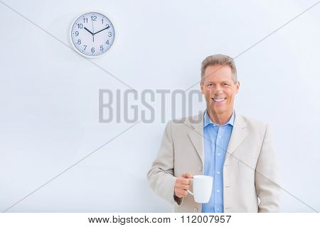 Smiling businessman holding a cup of coffee.