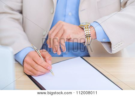 Businessman checking the time while doing paperwork.