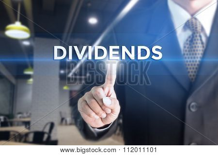 A Businessman holding a white sign with the message DIVIDENDS.