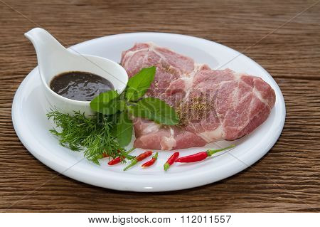 Fresh raw pork with pepper souce on wooden background