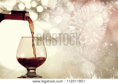 Red wine against silvery fireworks and holiday lights