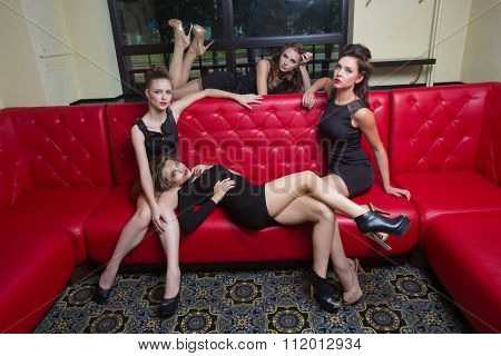 Four sexy girls on a red couch. in the interior