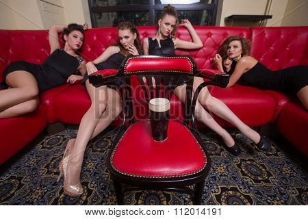 Four sexy girls on a red couch. in the interior. on the chair is a glass of beer