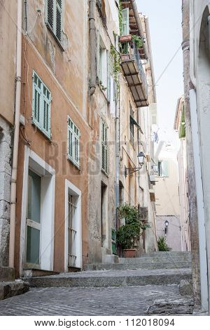 Narrow street with old buildings in medieval town Villefranche-sur-Mer on French Riviera, France.