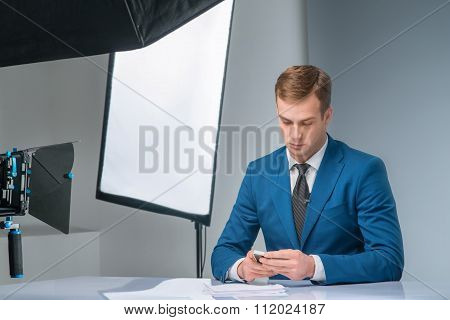 Newsman checking his smartphone
