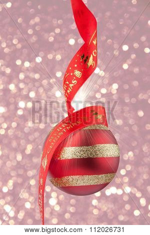 Christmas Bauble With Red Ribbon On Confetti Background