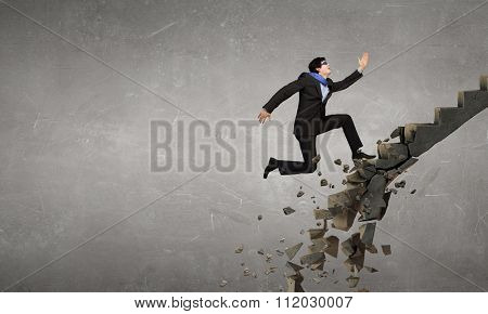 Young businessman walking up collapsing staircase representing success concept