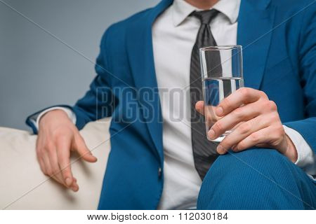 Handsome man holding a glass of water.