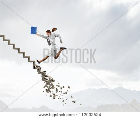 Young businesswoman walking up collapsing staircase representing success concept