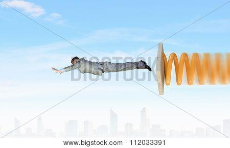 Businessman jumping on springboard as progress concept