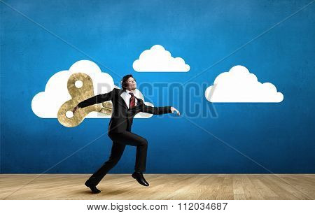 Young businessman walking with wind up key in his back