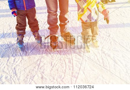 father with kids skating in winter, family winter sport