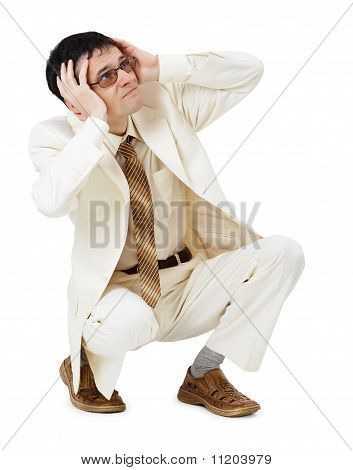 Scared Young Man In White Suit Sits