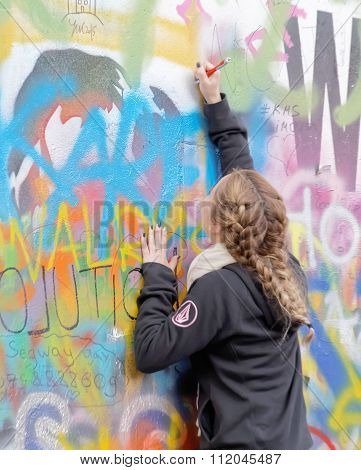 Woman Writes On Colorful Graffiti Wall