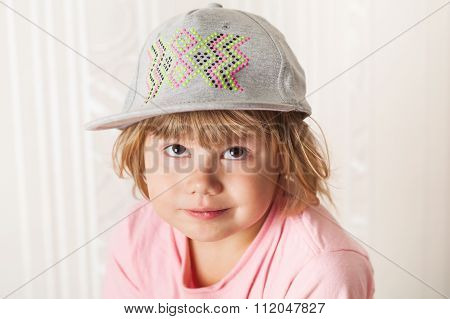 Confused Caucasian Blond Baby Girl In Gray Cap