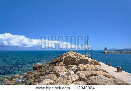 Sailboat at the stone breakwater in the harbor