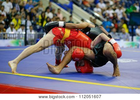 JAKARTA, INDONESIA - NOVEMBER 18, 2015: Ji Hui Zhu of China (red) fights Yosef Neonnub of Indonesia (black) in the men's 48kg Sanda event finals at the 13th World Wushu Championship 2015 in Jakarta.