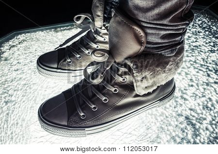 Warm Sneakers, Sporty Shoes Standing On Cracked Glass