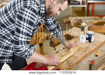 Craftsman sanding a guitar neck in wood at workshop