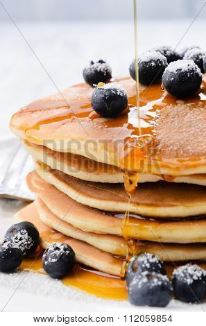 Delicious pancakes stack with fresh blueberries and pouring maple syrup