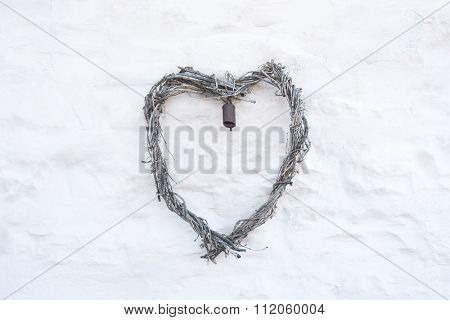 Rustic heart shape made from twig branches hanging on farmhouse country whitewash wall, background for wedding invitation or card