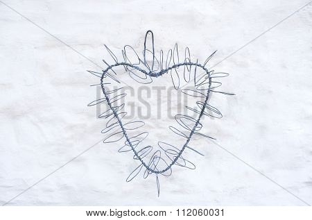 Artistic heart shape made from twisted wires hanging on farmhouse country whitewash wall, background for wedding invitation or card