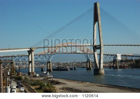 three large bridges over a river with a train on one bridge