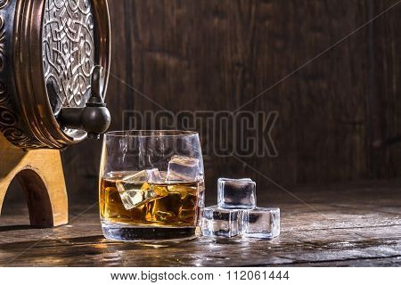 Copper Forged Barrel And A Glass Of Whiskey And Ice On A Old Table