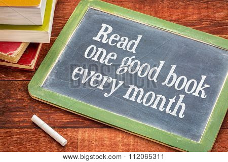 Read one good book every month - advice or reminder on a slate blackboard with a white chalk and a stack of books against rustic wooden table