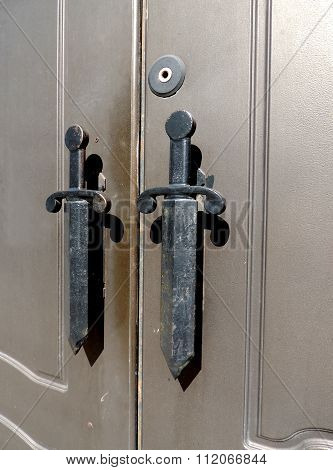 Fragment of metal doors with handles in the form of daggers