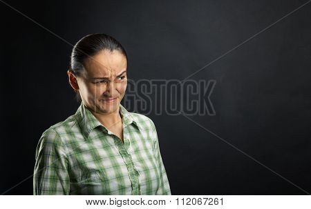Disgusted woman standing over black background