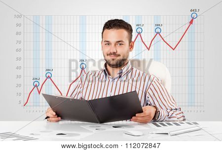Young businessman calculating stock market with rising graph in the background