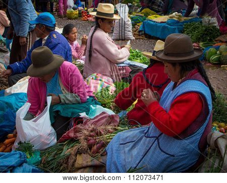 Pisac, Peru - May 17, 2015: Women selling produce at Pisac Market in the Sacred Valley of Peru.