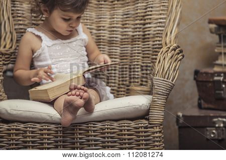 Cute Little Girl Child In A Chair, Reading A Book In  Interior