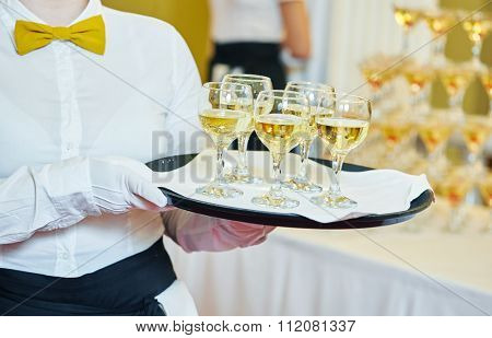catering or celebration concept. female waitress holding a tray with glasses of wine at party, Authentic shot in mixed light conditions