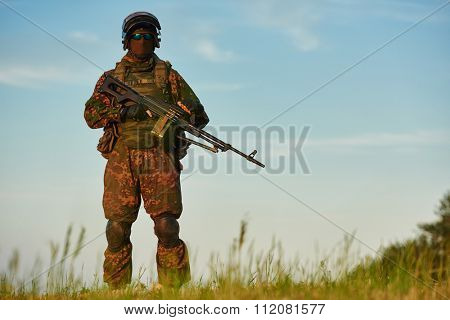 military. soldier in uniform with machine gun or assault rifle at summer evening sunset