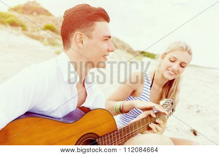 Happy romantic young couple playing guitar on beach in love