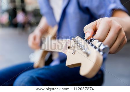 Hands of musician tuning his guitar outside