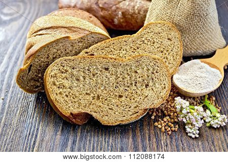 Bread buckwheat with cereals and flower on dark board