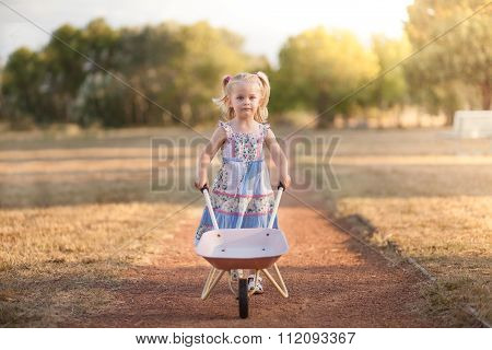 little girl pushing a wheel barrow outside