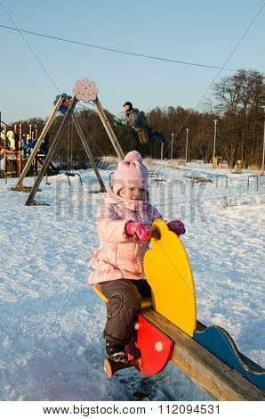 Children Swinging On A Swing In Winter