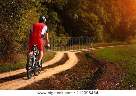 Cyclist with His Bike on the Autumn Meadow