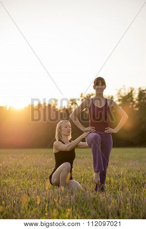 Female Pilates Trainer Making Corrections To Her Trainee As They Exercise Outside