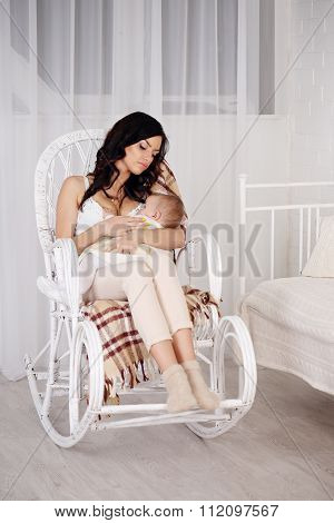 Woman and new born relax in a white bedroom
